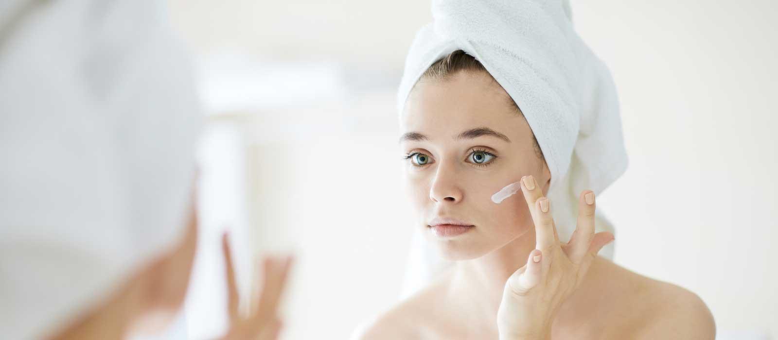 Symbolfoto für BIODERMA zeigt eine junge Frau beim Eincremen vor einem Spiegel