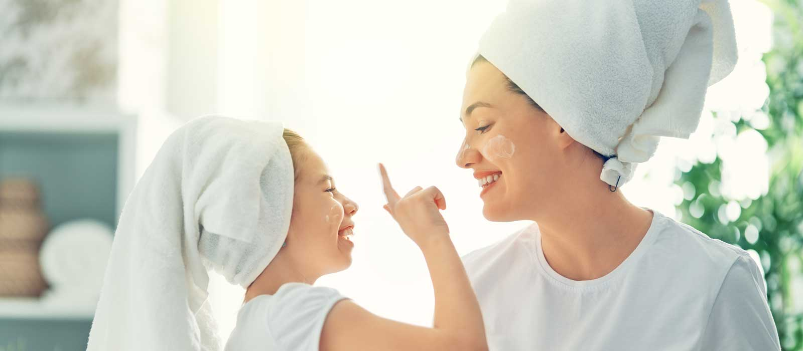 Symbolbild DERMASENCE zeigt eine Mutter mit der Tochter beim Eincremen