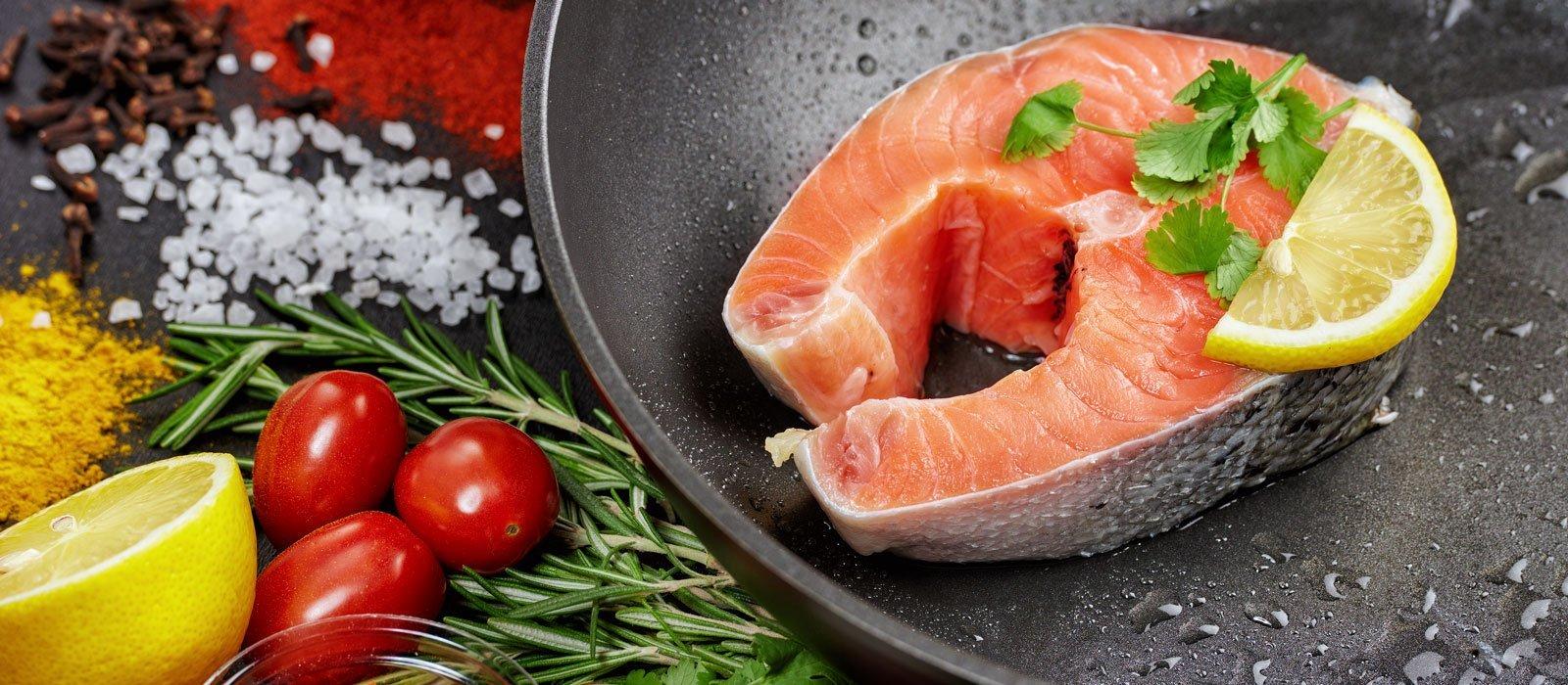 Symbolbild Ernährung zeigt eine Pfanne mit gekochtem Lachs und Gewürze und Früchte
