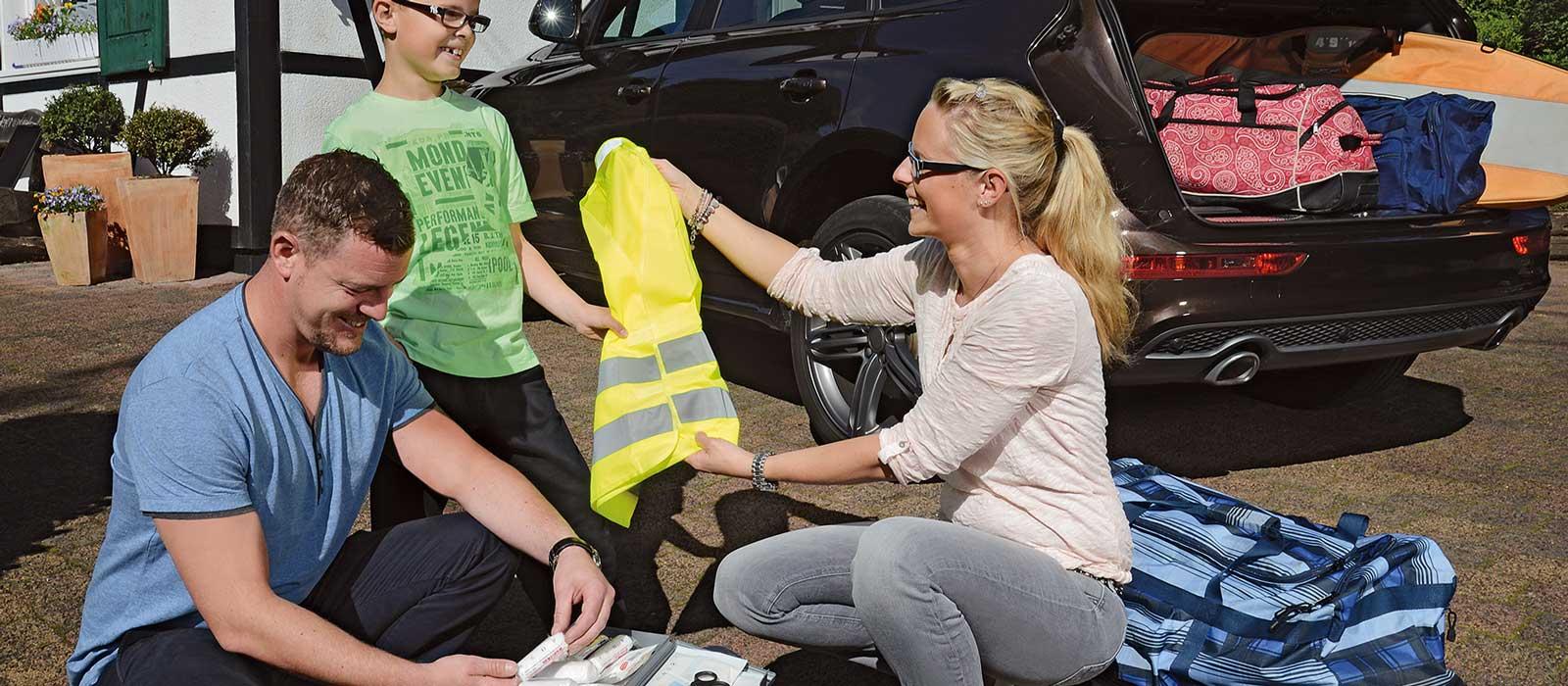 Symbolfoto Verbandkastencheck zeigt eine Familie beim Prüfen des Verbandkasten