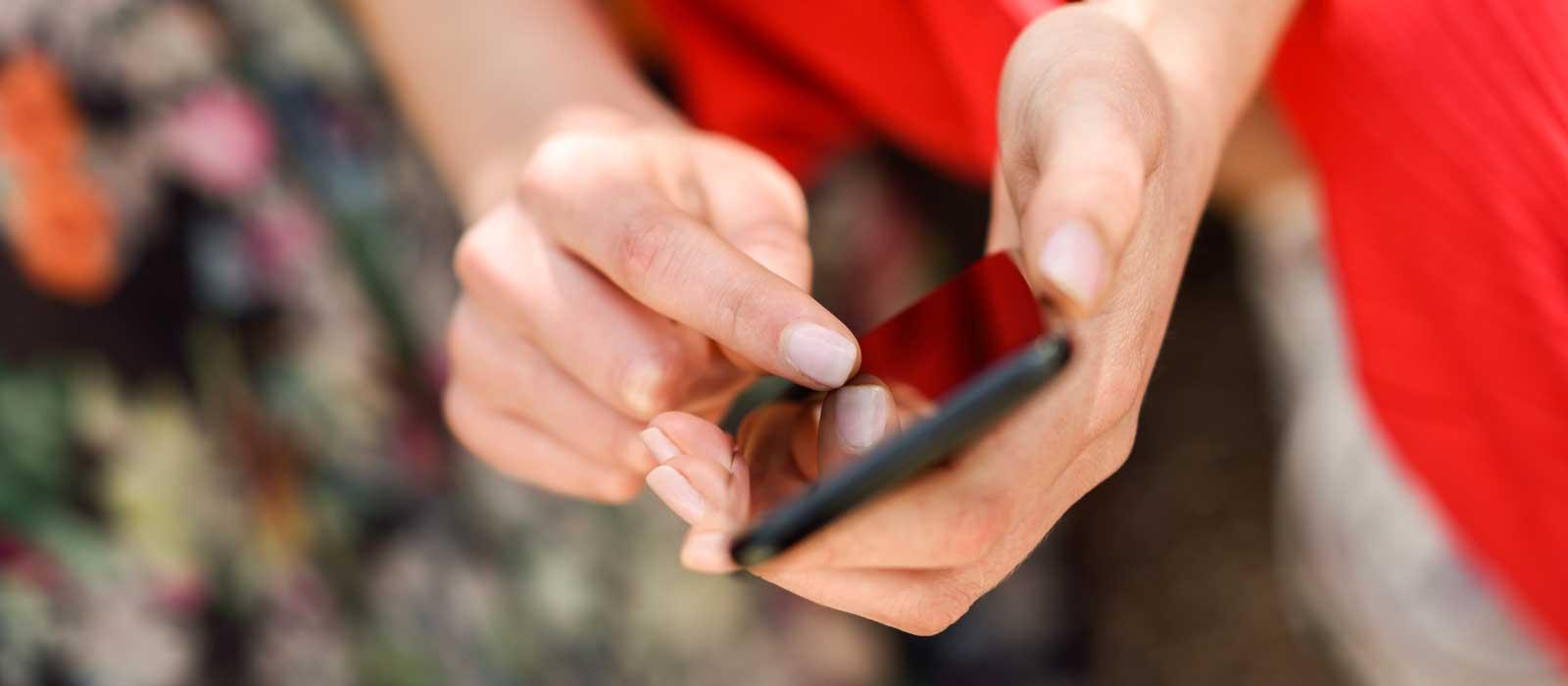 Symbolbild Arzneimittelvorbestellung zeigt eine Frau, die ein Smartphone benutzt