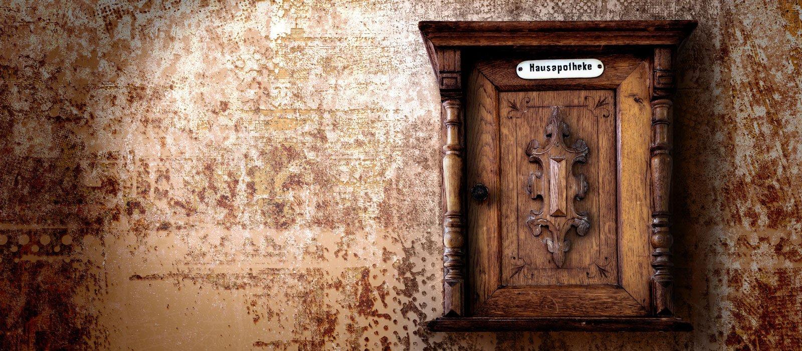 Symbolfoto zeigt eine hölzerne Hausapotheke an einer alten Wand