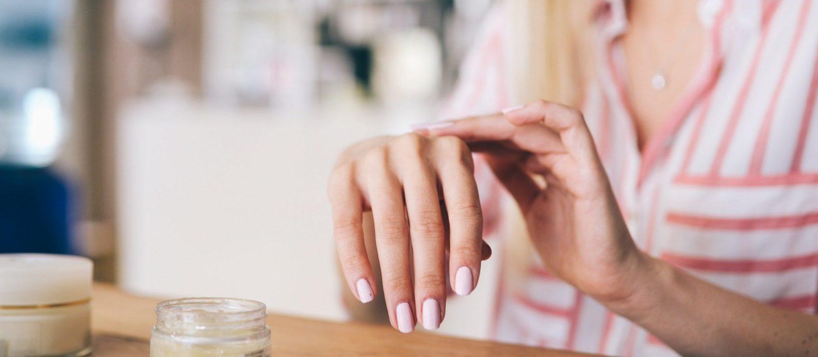 Symbolbild Kosmetik zeigt eine Frau, die eine Feuchtigkeitscreme auf die Hand aufträgt