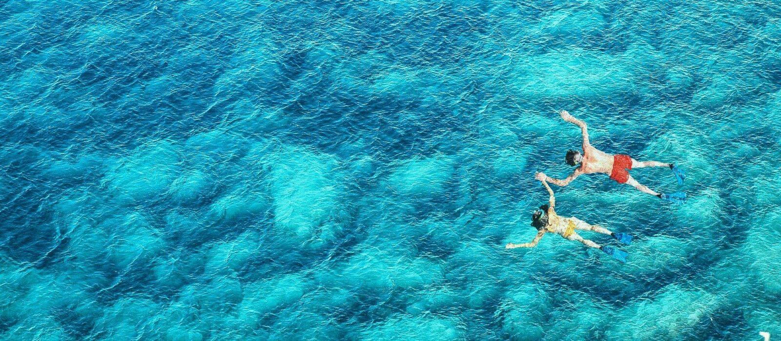 Symbolbild Reise- und Impfberatung zeigt zwei Personen schnorchelnd im Meer
