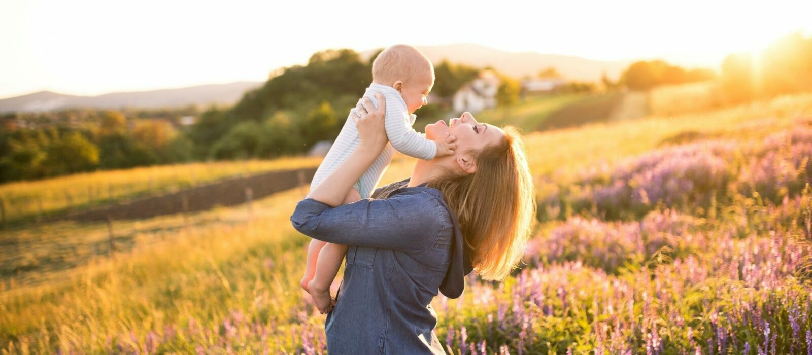 Symbolbild Weleda Naturkosmetik zeigt eine Frau auf einem Feld mit ihrem Sohn im Arm