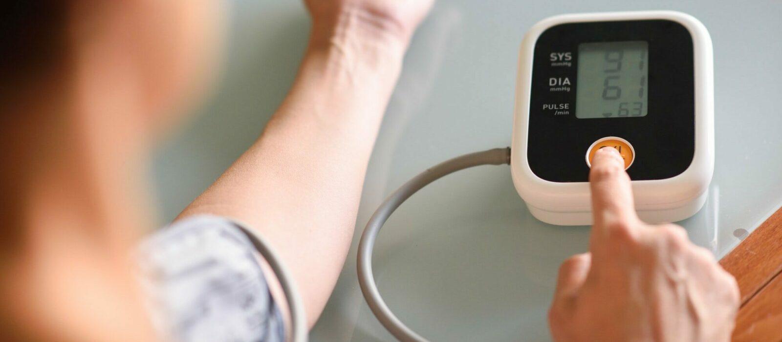 Symbolbild Blutdruckmessung zeigt eine Person, die sich den Blutdruck misst