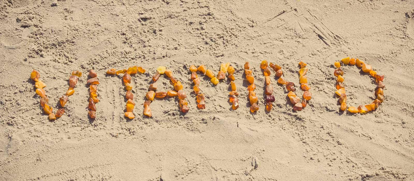 Symbolbild Vitamin D: zeigt den Text Vitamin D mit steinen im Sand